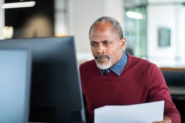 Ältere männliche Profi mit Computer im Büro – Foto