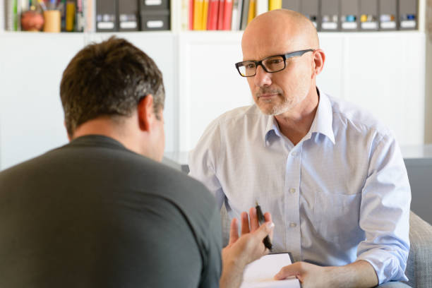 mature male psychotherapist working with client - psychiatrist stock photos and pictures