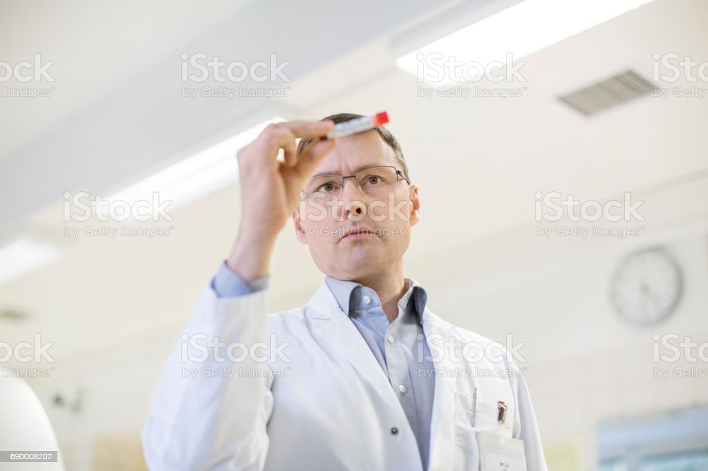 Mature male scientist analyzing medical sample royalty-free stock photo