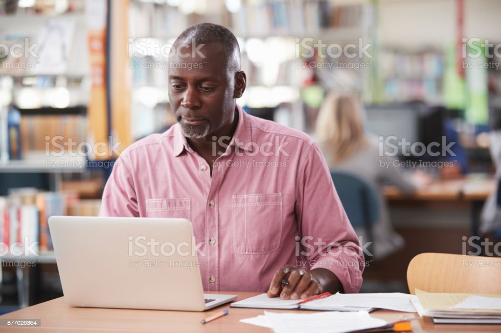 Mature Male Student Working On Laptop In College Library stock photo