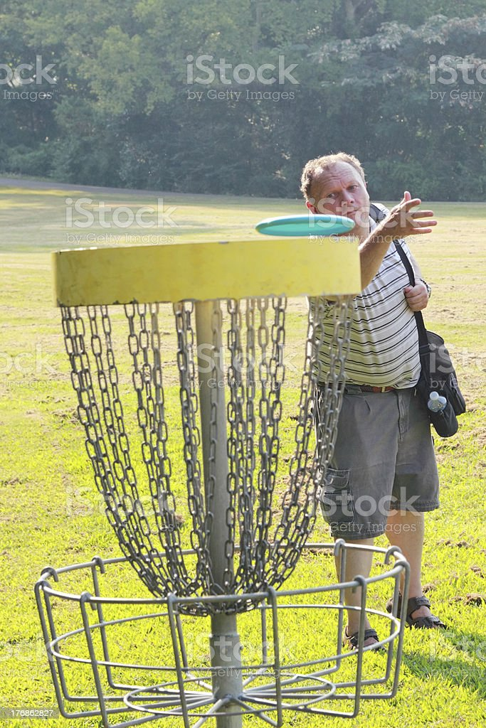 Mature Male Throwing Disc Golf Putt stock photo