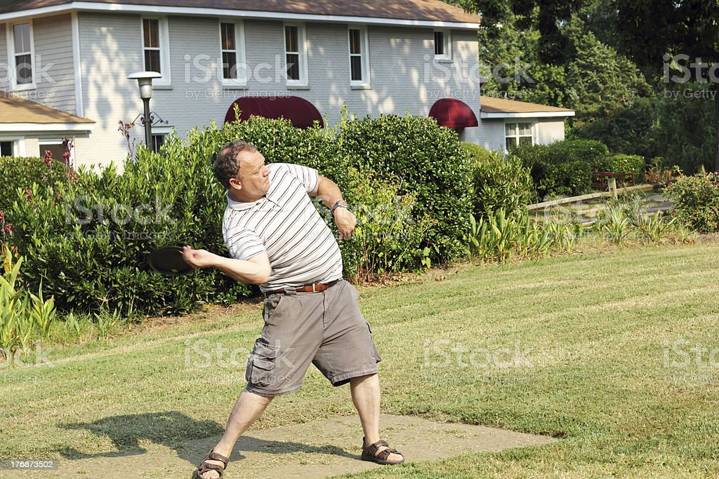 Mature male Throwing Frolf Driver from Tee stock photo