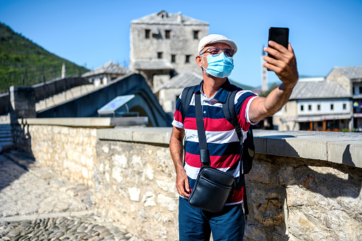 Mature male tourist with protective face mask taking a selfie at the Old Bridge, Mostar, Bosnia and Herzegovina.