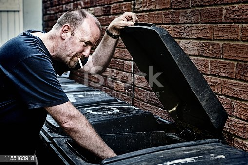 A scruffy, balding man, perhaps homeless, smokes a cigarette as he looks through an outdoor garbage can.