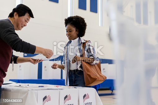 The mature adult male volunteer explains a voting document to the young female voter.