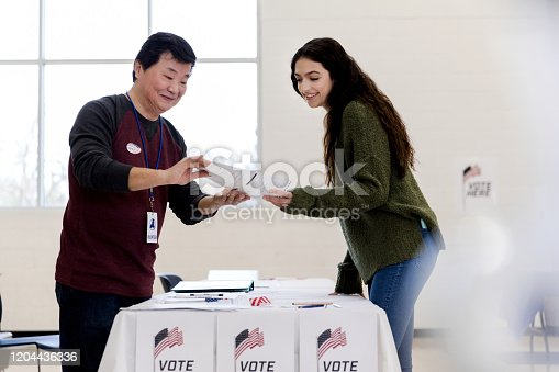 The mature adult male volunteer explains the documents the young woman needs to fill out to sign up to vote.