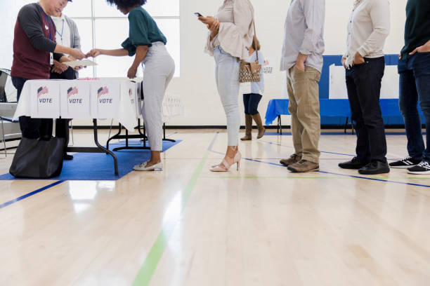 mature male volunteers help unrecognizable people lined up to vote - polling place stock pictures, royalty-free photos & images