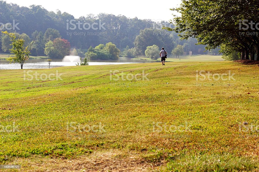 Mature Male Walking Frolf Fairway with Water Hazard stock photo