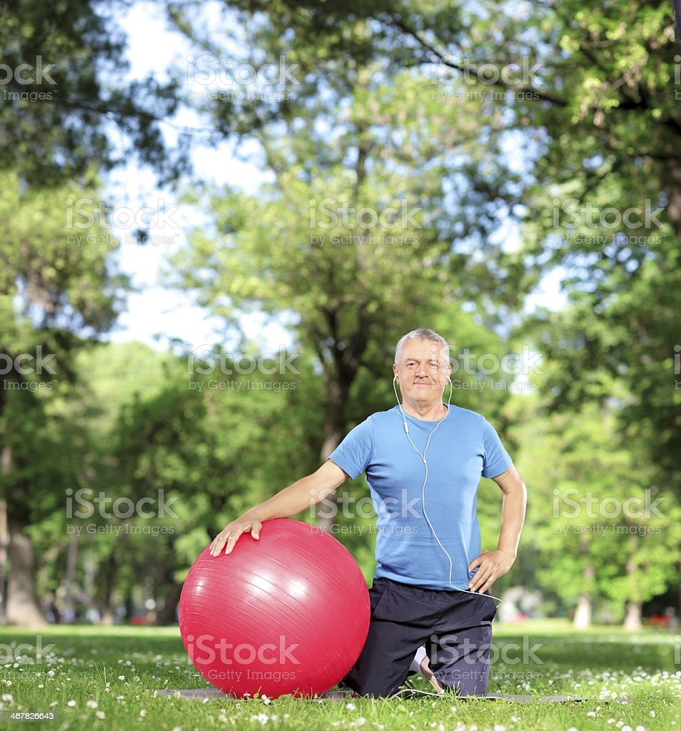 Mature male with an exercise ball in a park stock photo