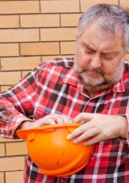 Mature man adjusting an orange hard hat stock photo