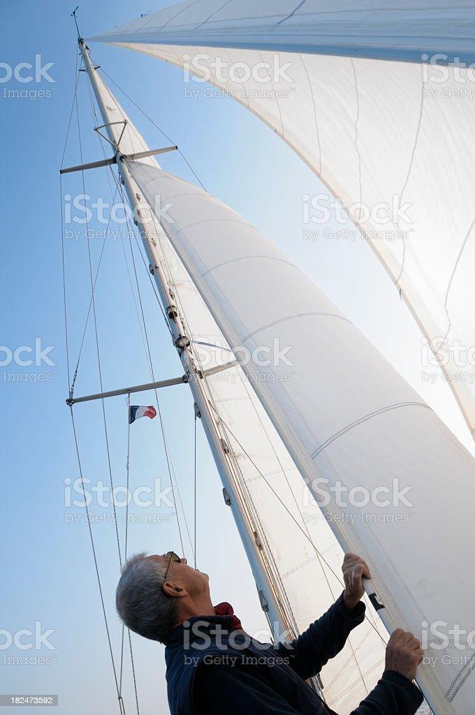 Mature man adjusting the sails royalty-free stock photo