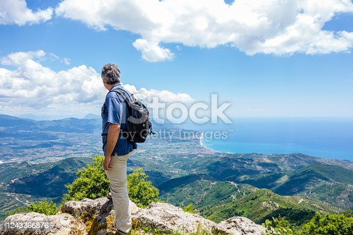 Mature man admiring stunning view of Cilento coastline from the top of a mountain.