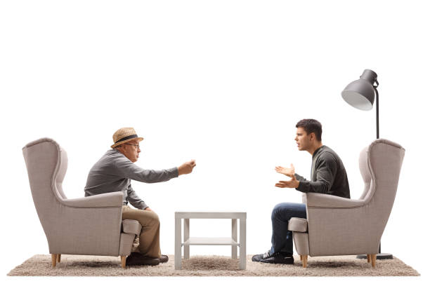 Mature man and a young guy seated in armchairs arguing stock photo