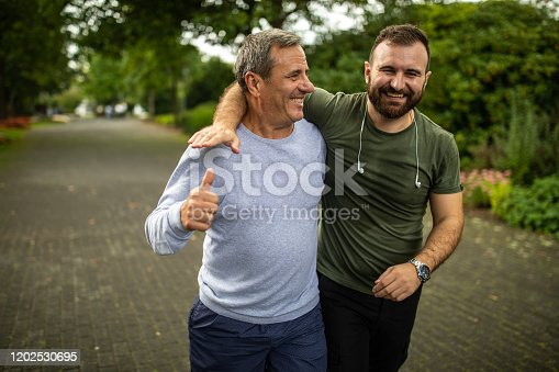 Mature man and his son jogging in park on autumn morning
