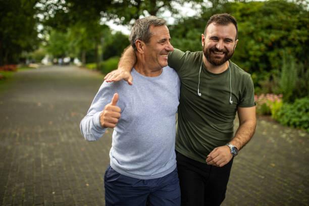 Reifer Mann und sein Sohn joggen am Herbstmorgen im Park – Foto