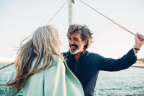 Senior couple in love enjoying cruising on their yacht.