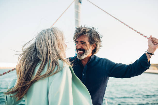Mature man and his wife enjoying sailing with their yacht stock photo