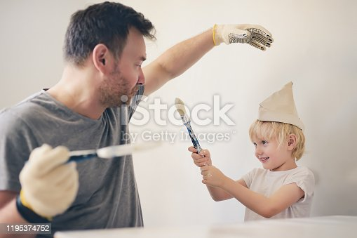 657926276 istock photo Mature man and little boy having fun with paint brush during repair of room together. 1195374752