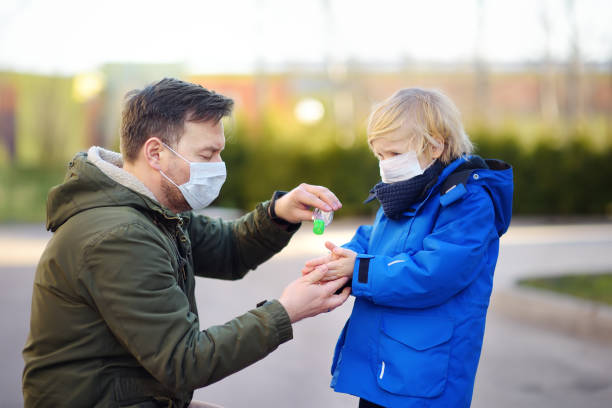 Mature man and little child wearing a protective mask makes disinfection of hands with sanitizer in airport, supermarket or other public place. Safety during COVID-19 outbreak. stock photo