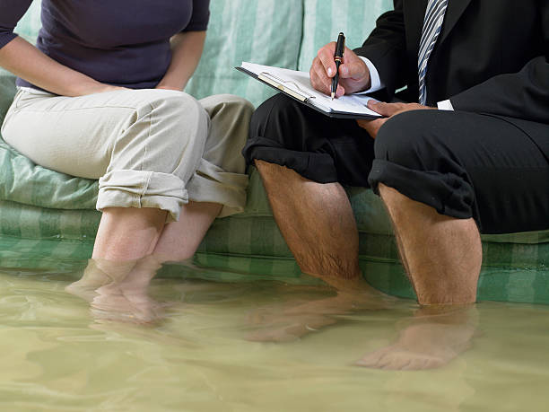 Mature man and mid adult woman sitting on sofa with water over their ankles, low section stock photo