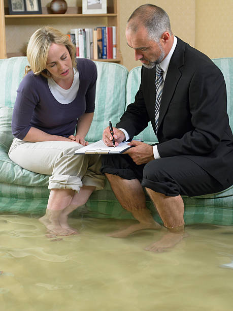 mature man and mid adult woman sitting on sofa with water over their ankles - flooded room stock photos and pictures
