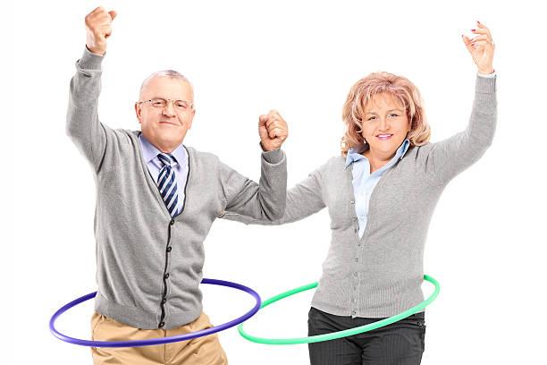 reifer mann und frau übungen mit hula-hoop - hula hoop workout stock-fotos und bilder