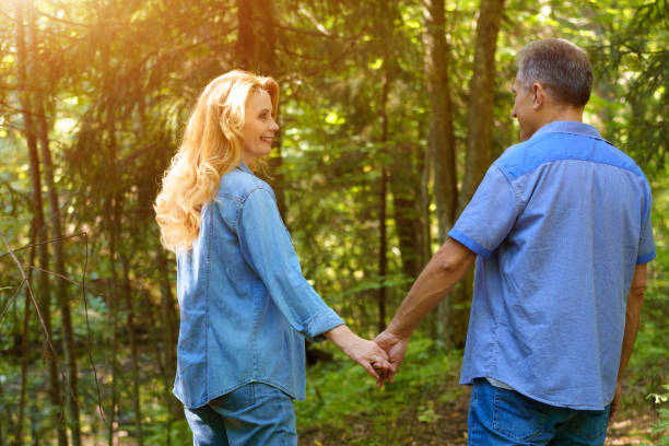 A Mature man and woman holding each other's hands are walking in the Park during the day. The concept of a happy retirement stock photo