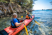 Mature man and mature woman kayaking in sea.
