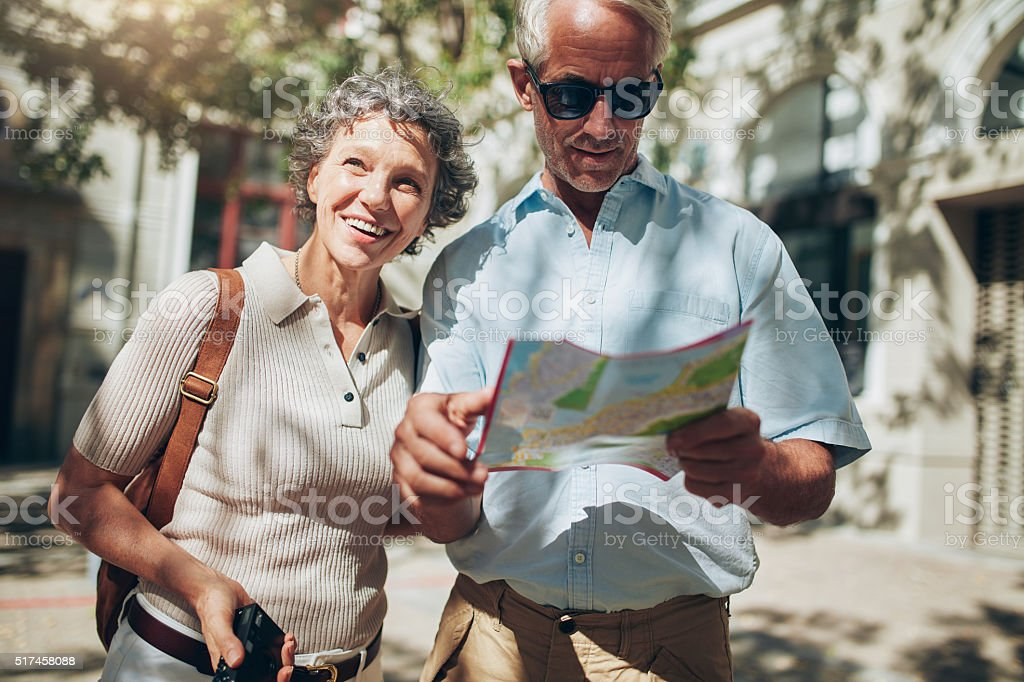 Mature man and woman using  map while sightseeing. stock photo