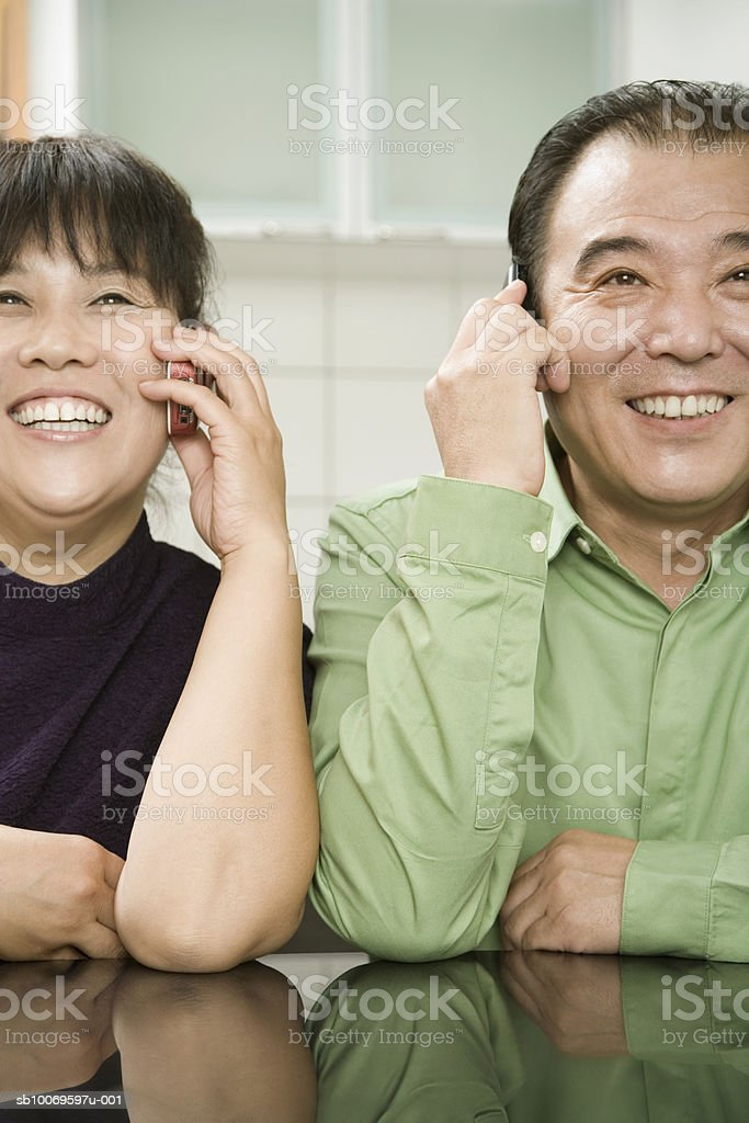 Mature man and woman using mobile phone, smiling photo libre de droits