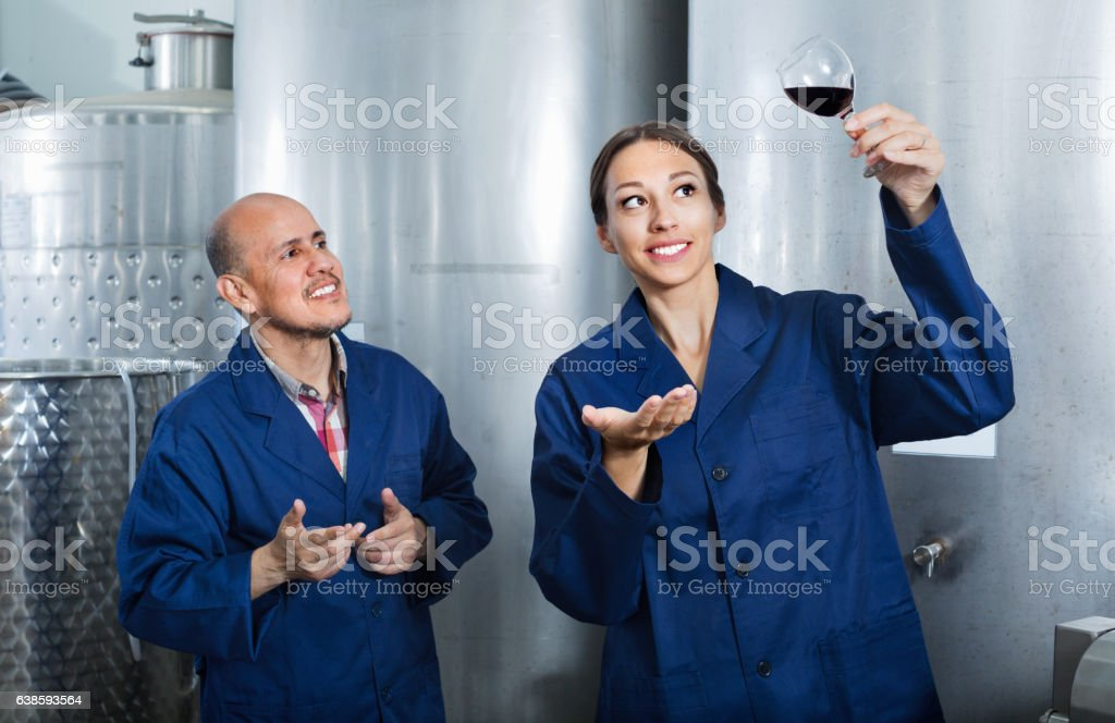Mature man and women coworkers looking at wine in glass stock photo