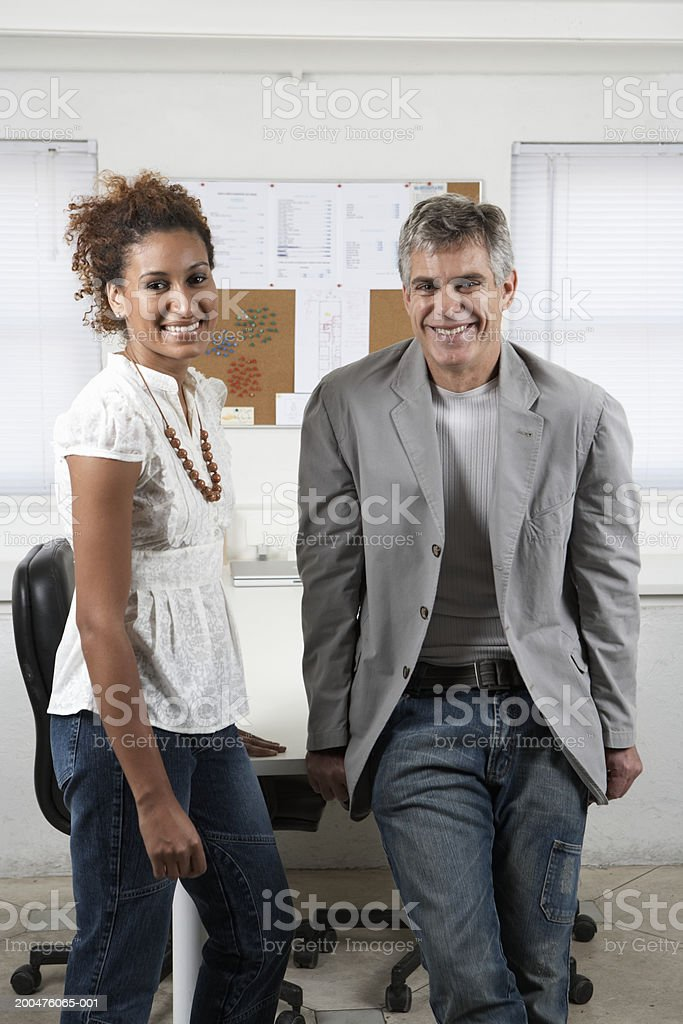 Mature man and young woman standing in office, smiling, portrait royalty-free stock photo