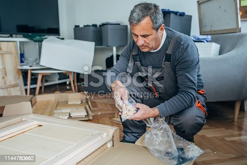 452592895 istock photo Mature man assembling new furniture for new home 1144780662