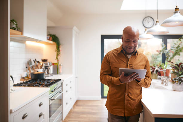 Mature Man At Home In Kitchen Looking At Digital Tablet stock photo