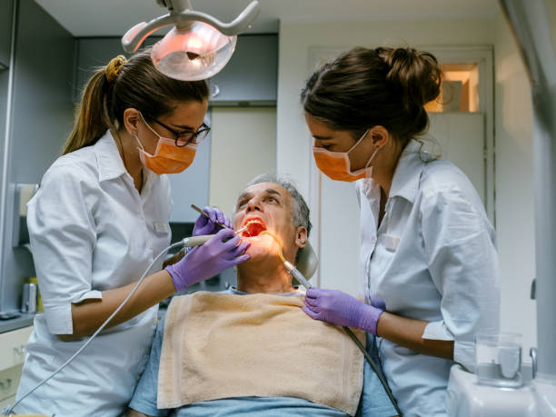 Mature man at the dentist Female dentist treating patient mature man teeth. tranquilizing stock pictures, royalty-free photos & images