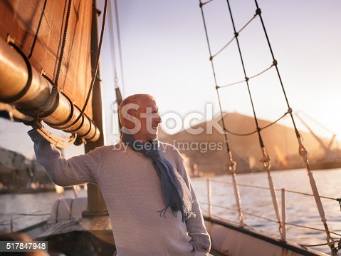 Retired mature man enjoying sailing on his yacht seen staring out at the ocean and enjoying the view