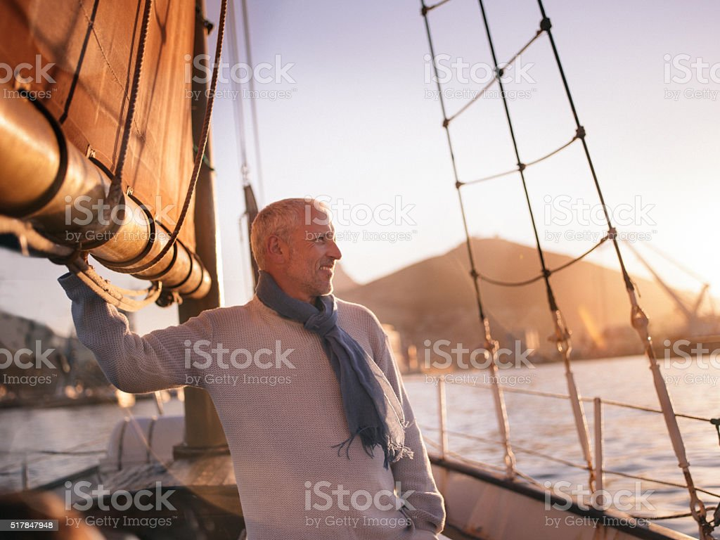 Mature man attending to ain sail and enjoying the view stock photo