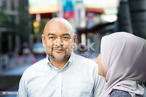 Mature man being congratulated by female friend as they walk down the street. She is smiling softly, looking away.