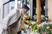 Mature man buying flowers in flower shop