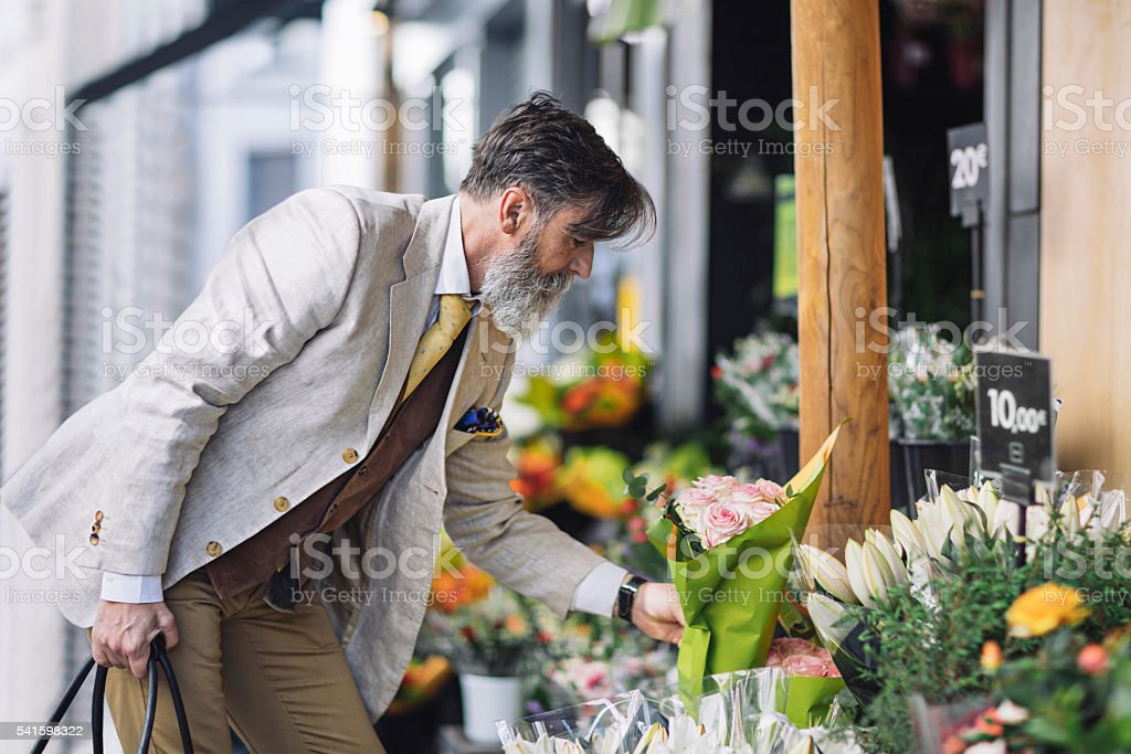Mature man buying flowers in flower shop stock photo
