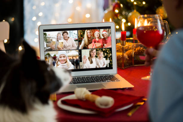 Mature man celebrating Christmas with his dog sitting at served holiday  table with laptop stock photo