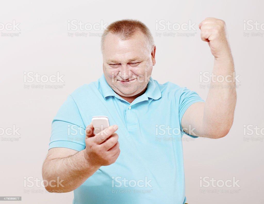 Mature man celebrating on his phone royalty-free stock photo