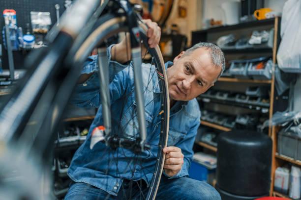cambio neumático de la bicicleta de hombre maduro - bastidor de la bicicleta fotografías e imágenes de stock