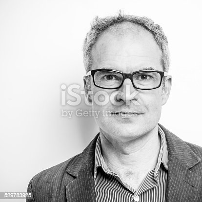 Mature man wearing glasses, slightly balding but not bad looking. Head and shoulders character portrait. Black and white square composition, cropped off centre.