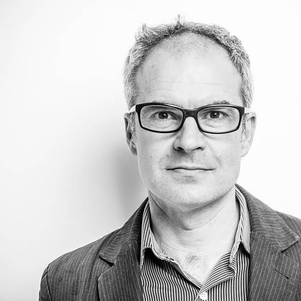Mature man - Character portrait Mature man wearing glasses, slightly balding but not bad looking. Head and shoulders character portrait. Black and white square composition, cropped off centre. monochrome stock pictures, royalty-free photos & images