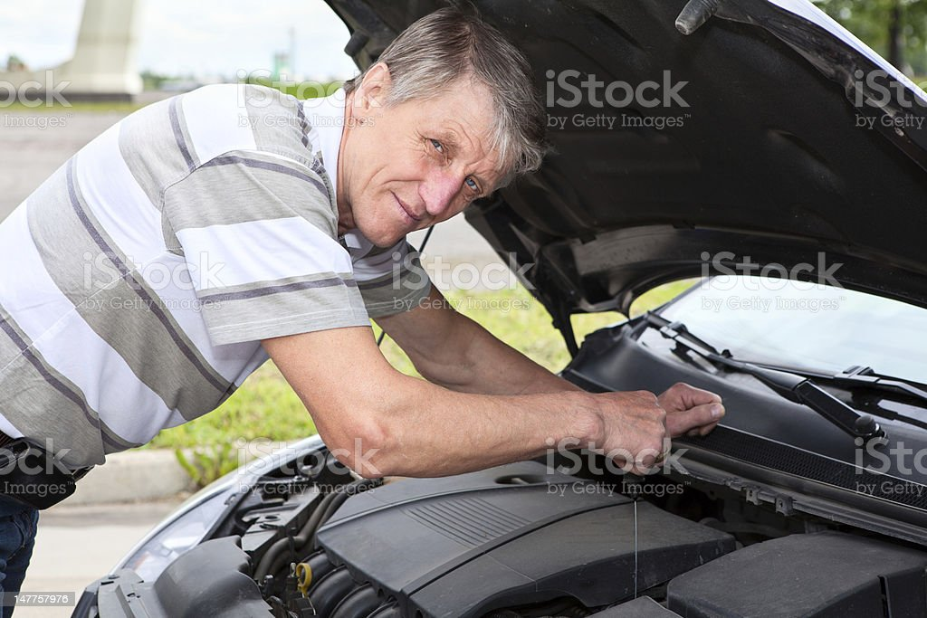 Mature man checking a oil level under car engine jacket royalty-free stock photo