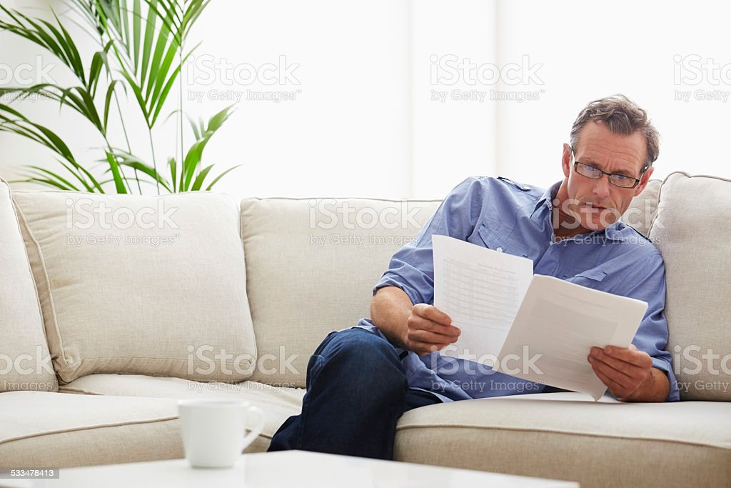 Mature man checking his monthly expenses bills stock photo