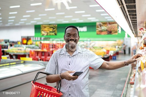 istock Mature man choosing products in supermarket 1184004777