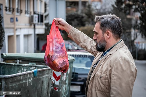Man hand holding garbage in bag for cleaning in to trash. Bearded Mid Adult Man Throwing Trash.