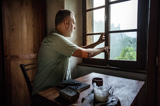 Mature Man Closing A Window On A Rainy Day Stock Photo - Download Image Now - iStock